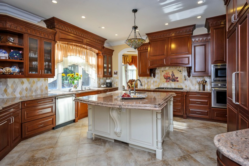 transitional kitchen design marble top kitchen island centered stained glass chandelier marble tiled floors glowing wood cabinets and display cabinets diamond shaped tiles backsplash