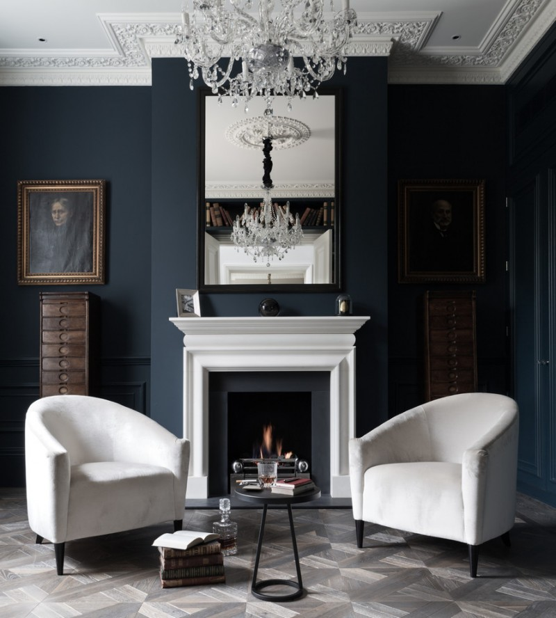 transitional living room with dark charcoal walls standard fireplace with white surrounding crystal chandelier white classic tub chairs black small center table