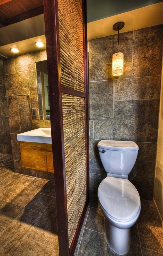 tropical bathroom design bamboo room partition with dark wood frame white toilet grey tiled walls grey tiled floors yellow light fixtures floating wood bathroom vanity with white countertop