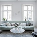 Ultra Light Blue Sofa With Lower Base Multicolored Throw Pillows Round Glass Top Coffee Table White Walls With Glass Windows Whitewashed Wood Siding Floors