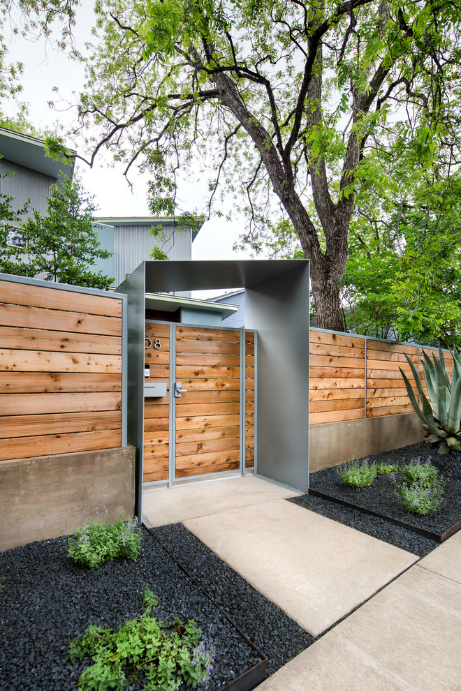 ultra modern front gate natural wood door panel and walls concrete walkway black ground planters