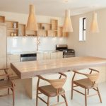 wall mounted table in large size wooden dining chairs light wood kitchen cabinets white painted walls white floors white ceramic backsplash wall mounted light wood shelves stainless steel kitchen appl