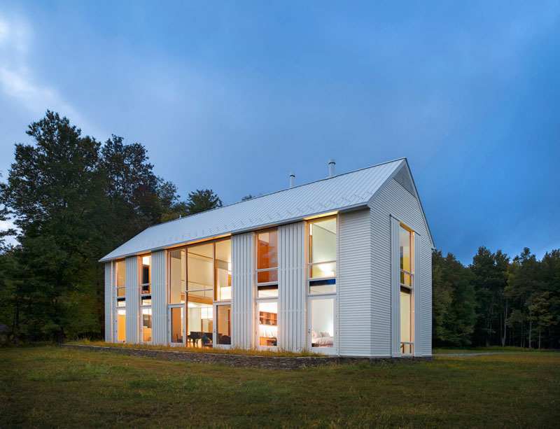 white modern farmhouse exterior with large glass windows and door