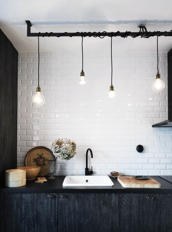 white subway tiled wall black countertop undermount sink in white black wrought iron faucet some pendants with black wires textural black cabinets