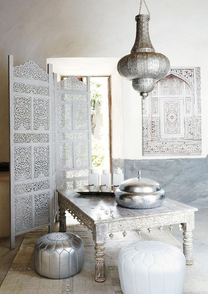 whitewashed square Moroccan coffee table with carving accents on bottom silver toned pouf seat carved partition in white white pouf seat