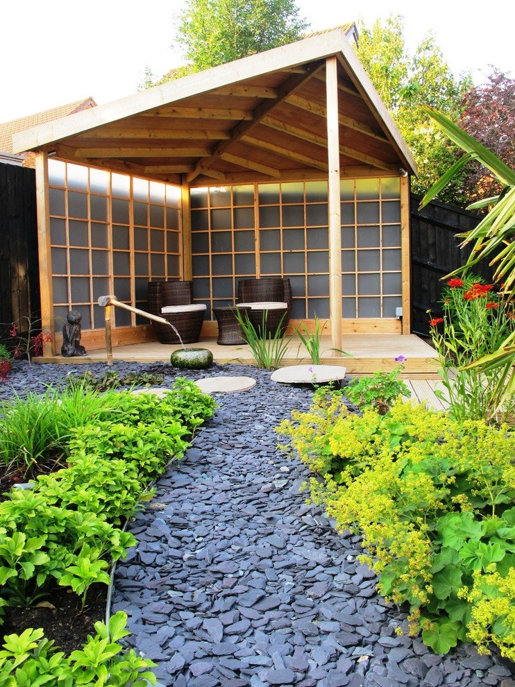 zen inspired patio with traditional fountain asian adopted landscaping idea dark rattan chairs dark finished rattan center table light wood constuction shoji screens