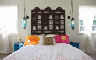 Mediterranean Moroccan bedroom idea dark finished Mashrabiya wood panel lantern shaped pendants in blue white bedding treatment flower pillowcased pillows dark neutral Moroccan pillow