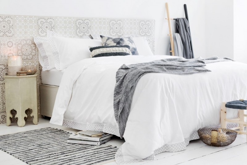 Scandinavian Moroccan bedroom idea white bedding treatment stripped monochromatic bed mat beige Moroccan side table geometric tiled walls