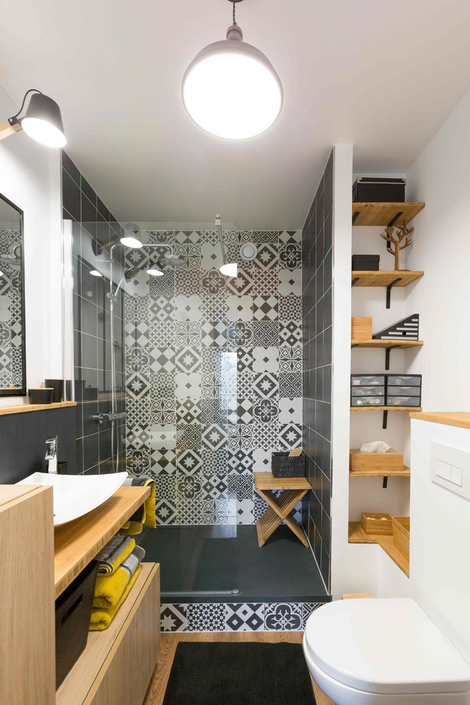 Scandinavian bathroom tiled wall with motifs plain black tiled walls wood shelving wall mounted toilet in white
