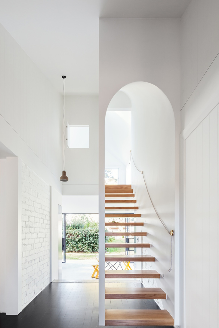 Scandinavian style hallway light wood steps curved top stairs white brick like walls dark wood floors white walls