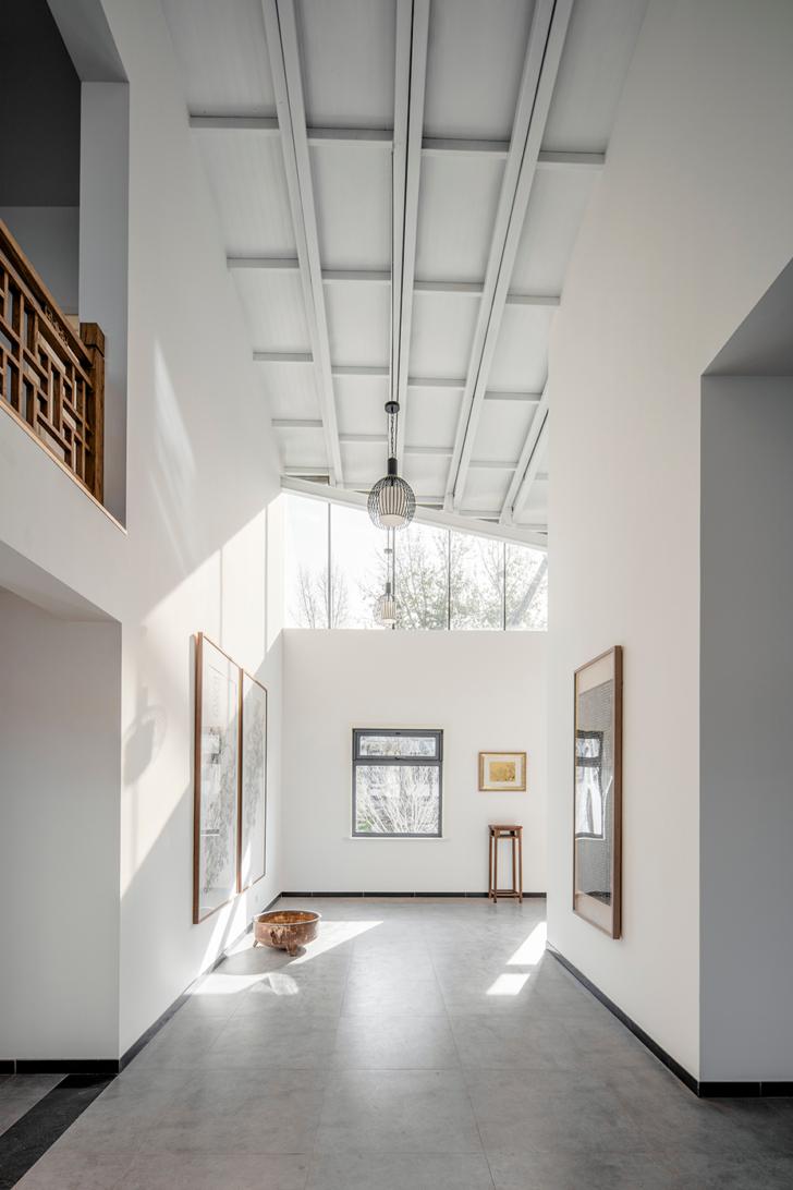artistic Scandinavian living room in plain color top glass windows higher ceilings in white light grey floors white walls wood framed wall arts