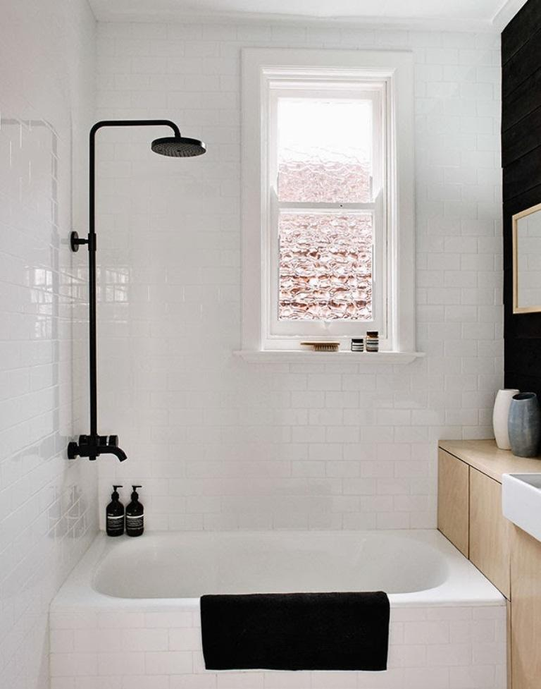 black and white Scandinavian bathroom medium sized built in bathtub in white black stained shower faucet black towel white ceramic subway tiles walls light wood vanity