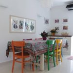 Eclectic Dining Room Colorful Wood Dining Chairs White Dining Table With Multicolored Skirt White Walls With Some Framed Wall Arts