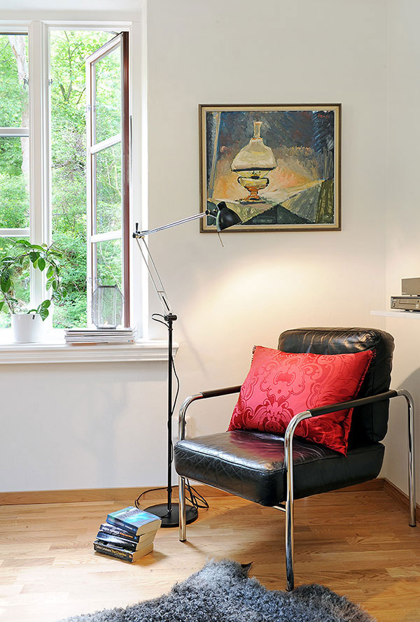 formal and simple reading nook black leather chair with red throw pillow modern floor lamp medium toned wood floors fury dark rug