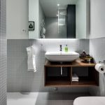 Gloomy Scandinavian Bathroom Gray Mosaic Tiled Walls Large Frameless Mirror Floating Wood Vanity With Open Shelves White Sink Wall Mounted Toilet Gray Mosaic Tiled Floors