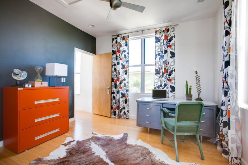 home office bright orange metal dresser silver toned metal working desk light green metal working chair cowhide rug medium toned wood floors multicolored curtains