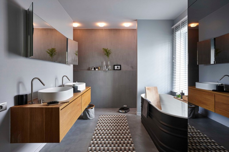 large and dark Scandinavian bathroom floating wood vanity double white sinks mirror with cabinets behind gray concrete walls and floors monochromatic run rug black bathtub