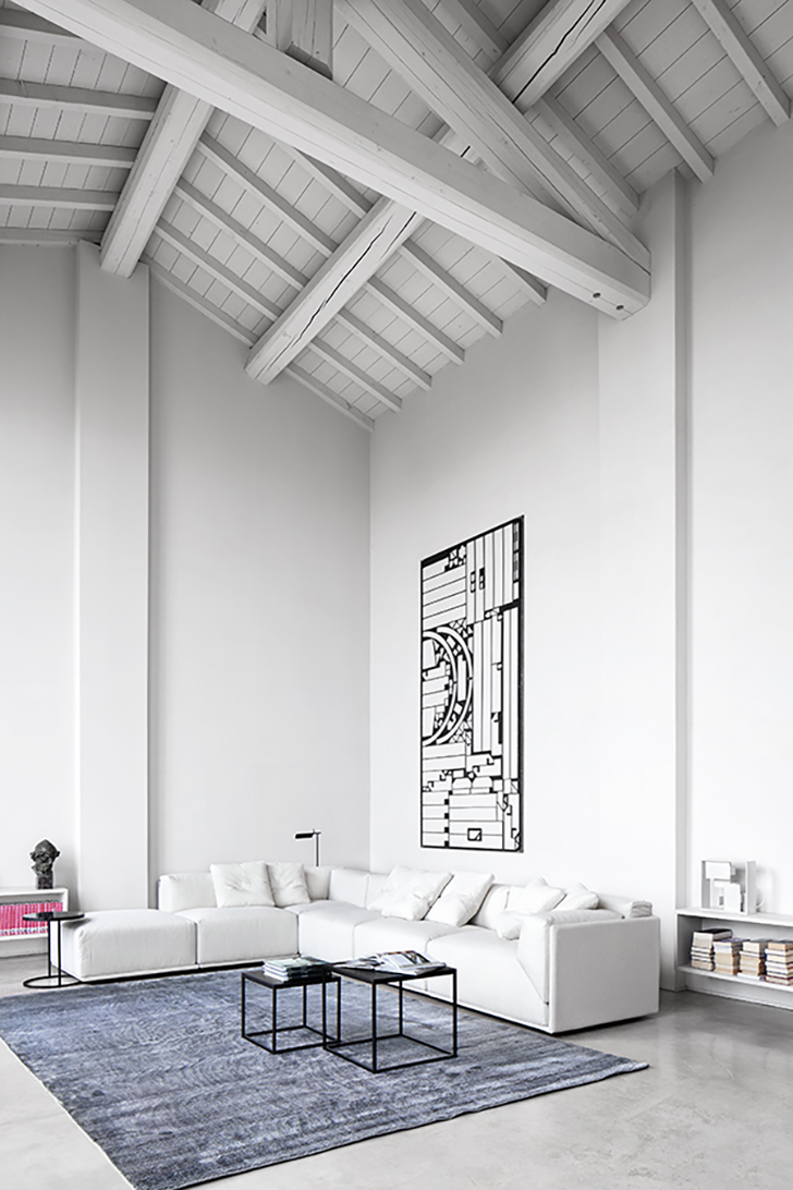 large and high formal living room in Scandinavian style white ceilings with exposed beams L shaped sofa with facing chaise blue velvet rug black wrought industrial coffee table huge pop art