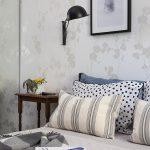 Light & Neutral Wallpaper With Gloss Silver Flower Motifs Black Wall Mounted Lamp Black Framed Wall Decor Wood Bedside Table