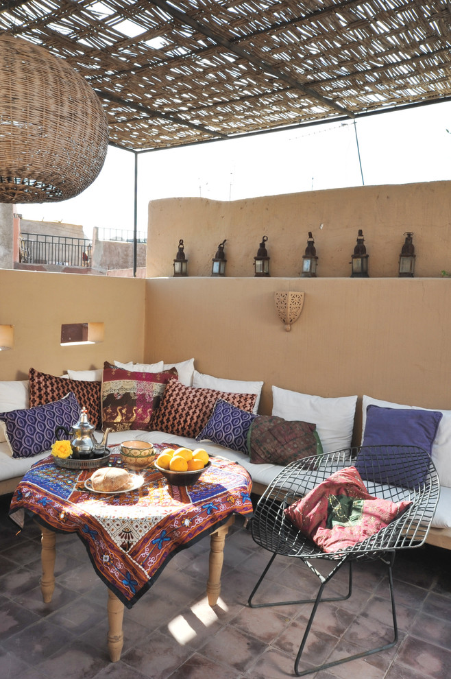 mediterranean Moroccan porch earthy brown walls shabbier gray tiles flooring colorful and patterned textiles on throws table skirt and cushion