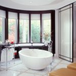 Modern Bathroom Idea Freestanding Marble Tub Marble Tiled Floors With Stone Accents Chrome Bathroom Appliances Dark Wood Framed Windows