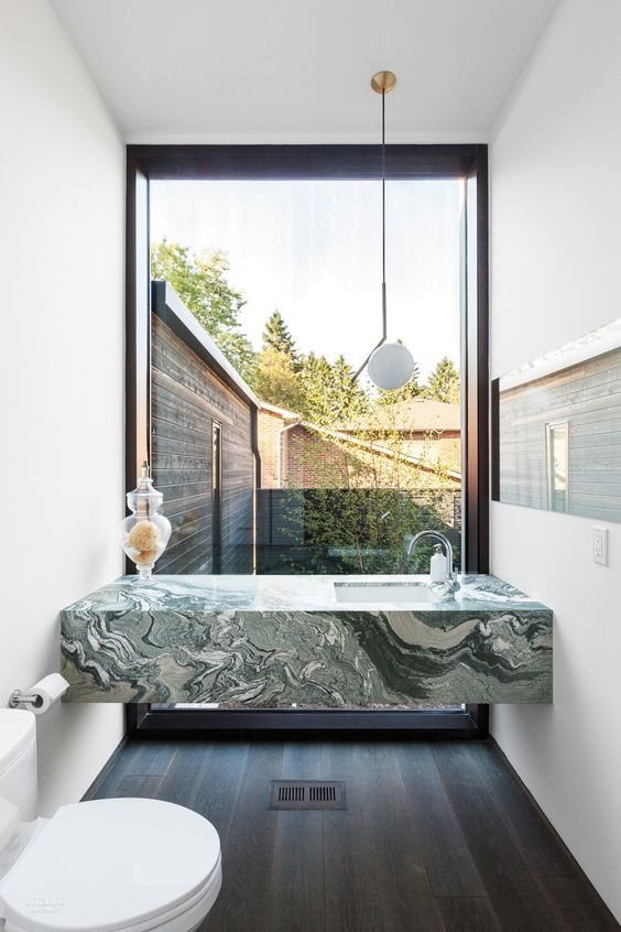 modern bathroom idea green marble bathroom vanity white undermount sink white toilet dark wood plank floors white walls giant glass window with black frame
