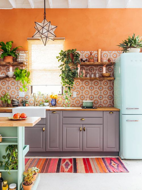 modern bohemian kitchen idea orange wall color flower patterned tiles for backsplash gray kitchen cabinets wood countertop ethnic runner houseplants