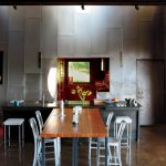 Modern Industrial Dining Room Iron Planks Wall White Modern Dining Chairs Modern Wood Dining Table Exposed Iron Beams Dark Neutral Floors