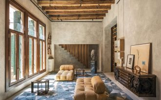 modern rustic living room with concrete walls wood windows' trims wood stair's railings exposed wood beams earthy brown leather chaises textural blue white rug floating wood credenza with handcra