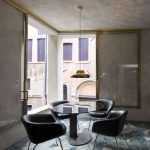 Modern Seating Area Modern Black Leather Chairs Round Glass Top Center Table Lower Industrial Pendant With Gold Toned Lampshade Concrete Walls Gold Toned Window's Trims