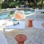 Pool Side Area White Outdoor Furnishings White Orange Throw Pillows Orange Side Table White Brick Floors