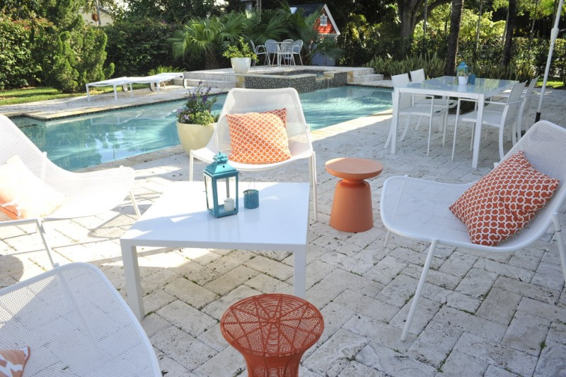 pool side area white outdoor furnishings white orange throw pillows orange side table white brick floors