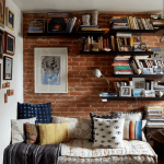 Reading Nook Wall Mounted Bookshelves Red Brick Wall Piled Daybed Mattresses Throw Pillows Striped And Textural Area Wood Floors