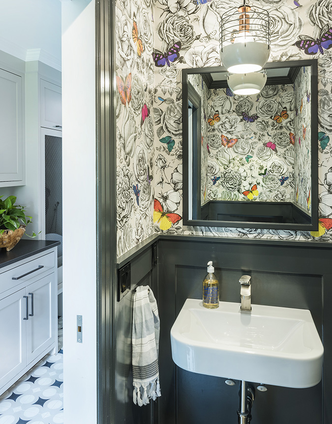 small bathroom design with crowded & bold toned wallpaper black framed mirror freestanding sink in white black baseboard