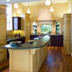 Traditional Eat In Kitchen With Green Marble Counter Wood Floors Warm Lighting Fixtures Light Toned Wall Color