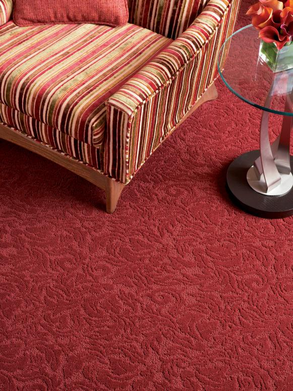 vivid red carpet with texture and pattern stripped chair round glass top side table with dark leg