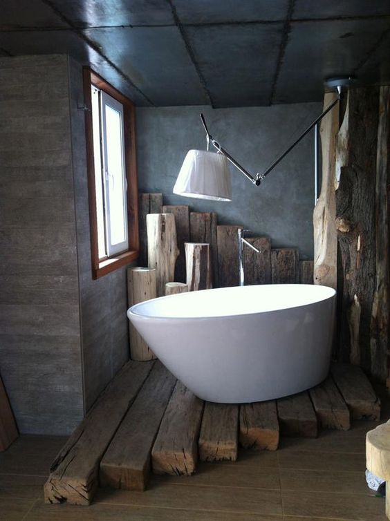 dark nuance bathroom  white bathtub modern lamp with white lampshade log floors dark toned concrete walls