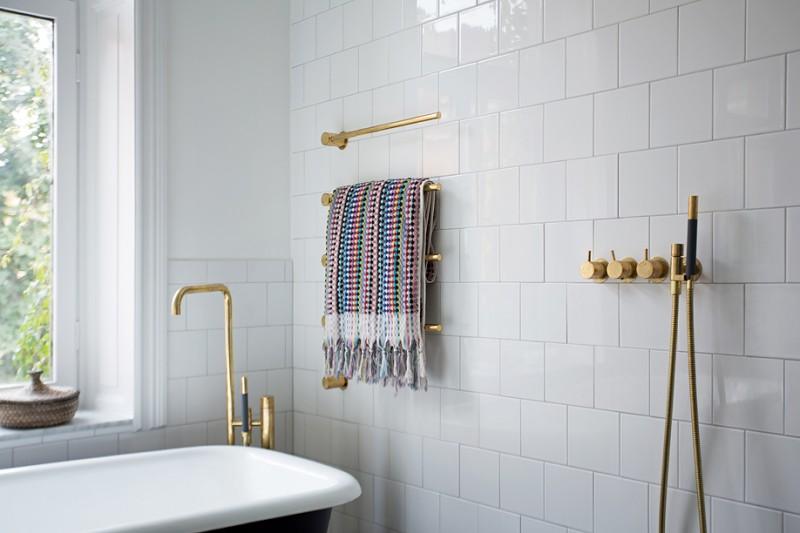 elegant and glam bathroom idea white subway ceramic tiles walls brass fixtures clawfoot tub