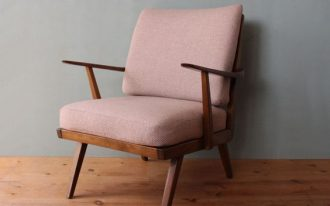 mid century modern chair with dusty pink upholstery and wood construction