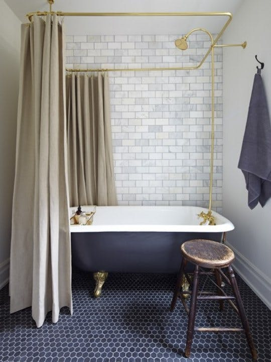 modern bathroom navy blue hexagon mosaic tiles flooring white subway tiles walls beige shower curtains clawfoot tub shabbier wood stool gold toned fixtures