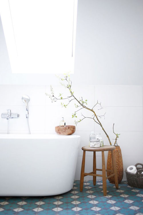 patterned tiled floors with blue and white white bathtub wood stool houseplant in wood vase skylight stainless steel fixtures