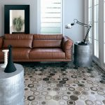 Simple Neutral Toned Living Room Earthy Brown Leather Sofa Silver Toned Side Table And Center Table In Cube Shape Hexagon Shaped Tiles In Gray