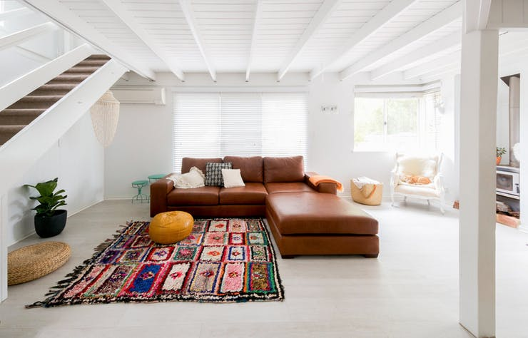 statement rug geometric accent table in orange leather couch with additional chaise light toned concrete floors white walls and ceilings