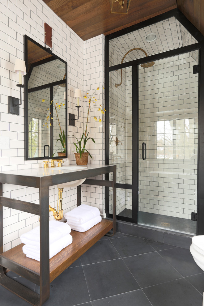 transitional bathroom white subway ceramic tiles walls black framed mirror black wood vanity with undermount sink black tiles flooring black framed shower glass paneling