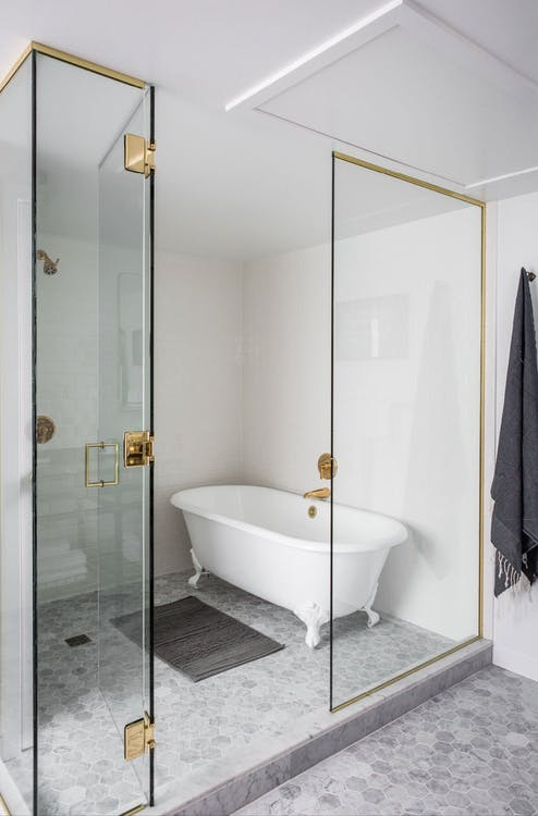 tub in shower space glass enclosed shower space with brass accent white clawfoot tub in white brass fixtures light floors bathroom mat in gray