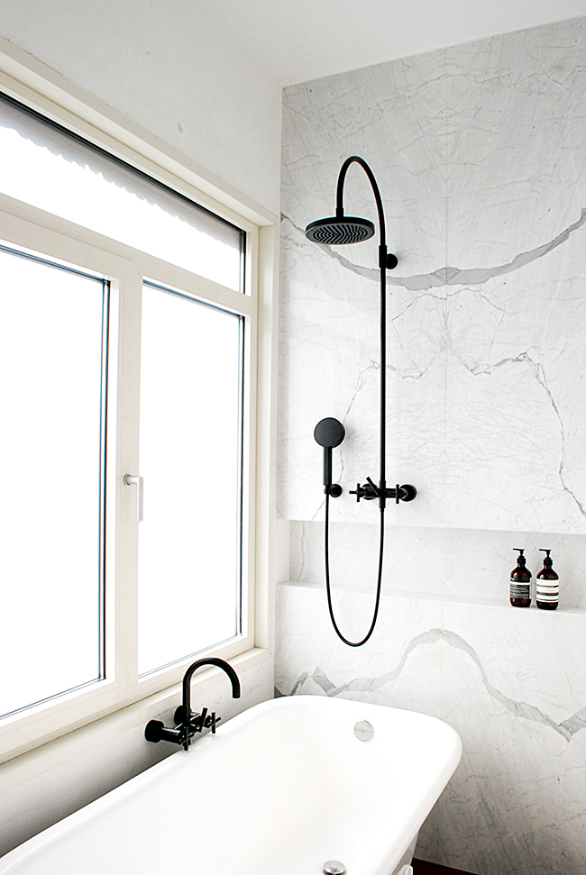 white bathroom with matte black fixtures white bathtub marble walls