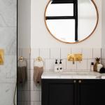 White Subway Tiles Wall Brass Framed Mirror In Round Shape Marble Countertop Black Cabinets Brass Sink Undermount Sink