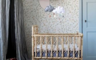 bamboo baby crib floral wallpaper light wood siding floors natural fiber basket decorative interior tent with light blue curtains