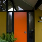 Bright Orange Front Door With Black Frame And Blury Glass Sidelight Yellow Wall Exterior