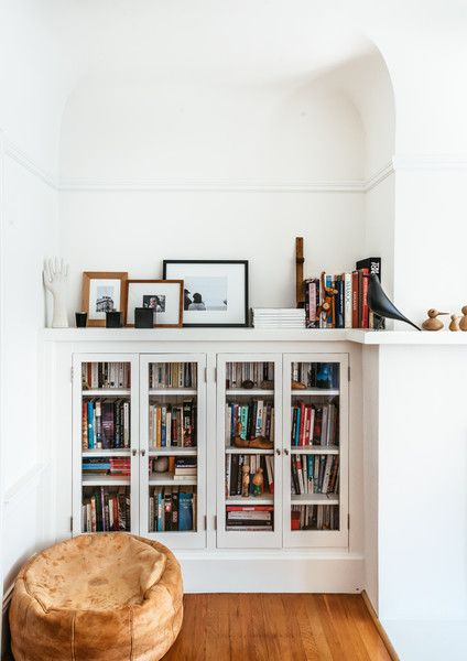 corner bookscase with glass door and additional display shelf on top leather pouf from Morocco
